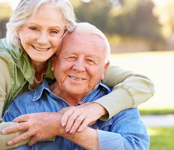 Image of smiling senior couple embracing each other.